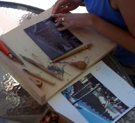 carving a linocut outside on a patio table