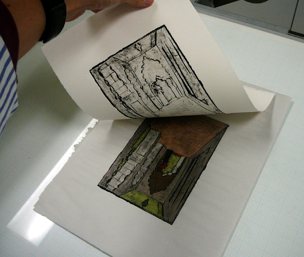 a hand lifting the printed paper off the inked plate after the two were pressed together