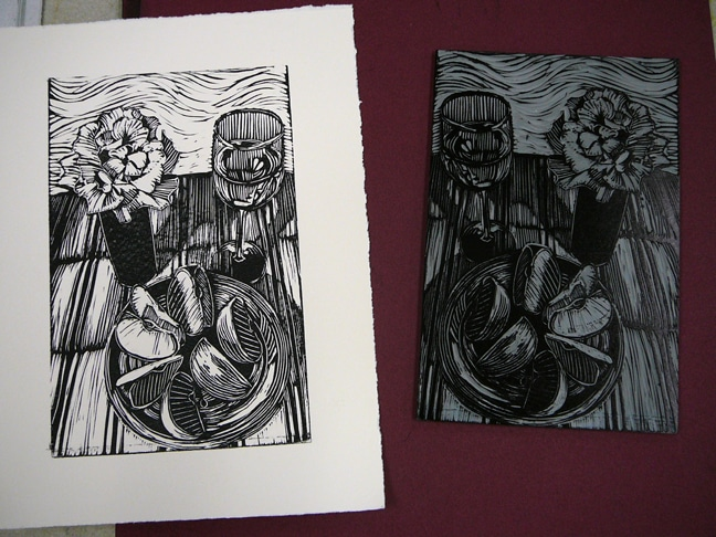 a black and white linocut of a still life with wine, apples and a rose next to the carved block it was printed from