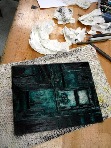blue green ink on a clear plexiglass plate being pushed around and moved to create an interior bathroom scene in the process of becoming a dark field monotype print