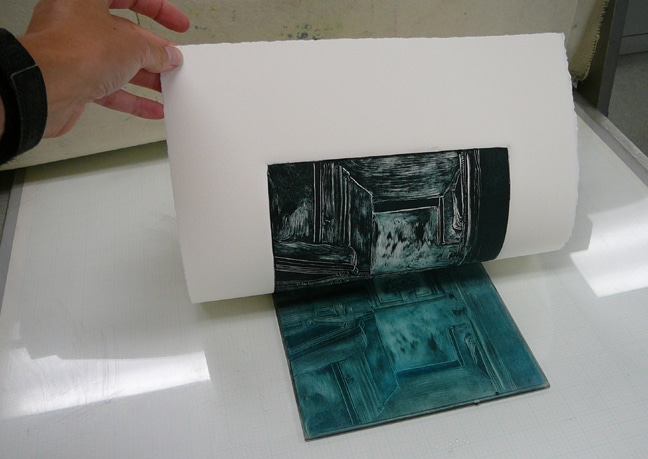 after moving wet ink around on a sheet of plexiglass, and rolling the still wet ink under the cylinder of an etching press against a sheet of printmaking paper, the paper is pulled from the plate to reveal the monotype print