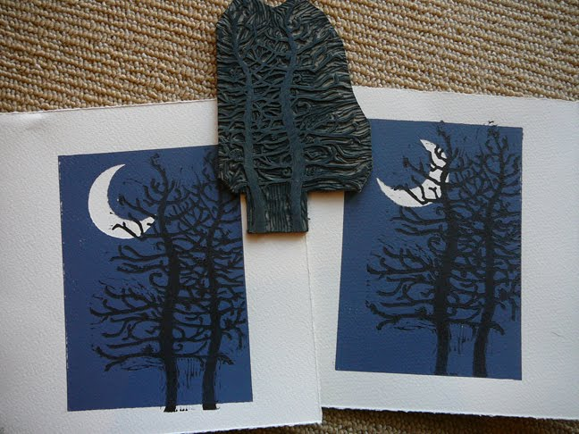 a linocut of a craggy old pine tree, printed on a dark blue background and a white crescent moon