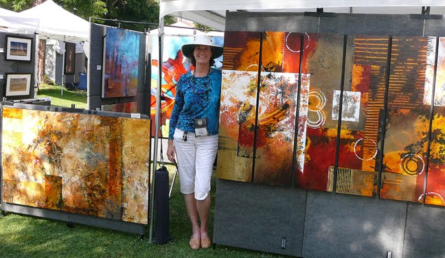 a woman standing in an outdoor exhibit booth, smiling, surrounded by large abstract paintings