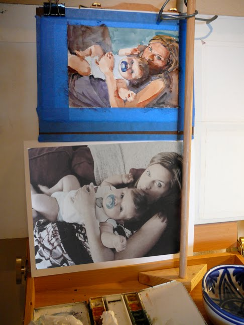 Reference photo and watercolor portrait or a mother and child in process in the art studio