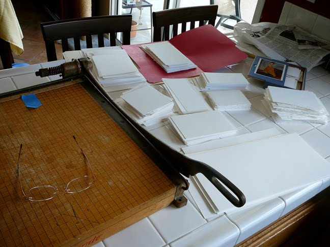 an old fashioned paper cutter and stacks of small squares of printmaking paper on a counter