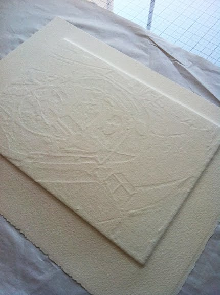 The back of a collagraph print, still pressed against the plate to show the amount f stretch required of the paper to reach the recessed areas.