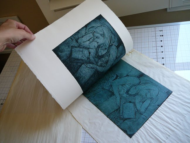 after a trip through the press, a mat board collagraph print is being pulled from the plate