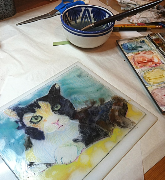 Adding watercolor to a monotype on plexiglass before printing against paper