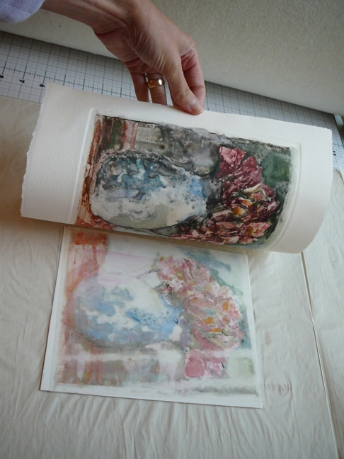 a hand pulling a sheet of printmaking paper off a printmaking plate (drafting mylar) to reveal of painterly print of a vase with roses
