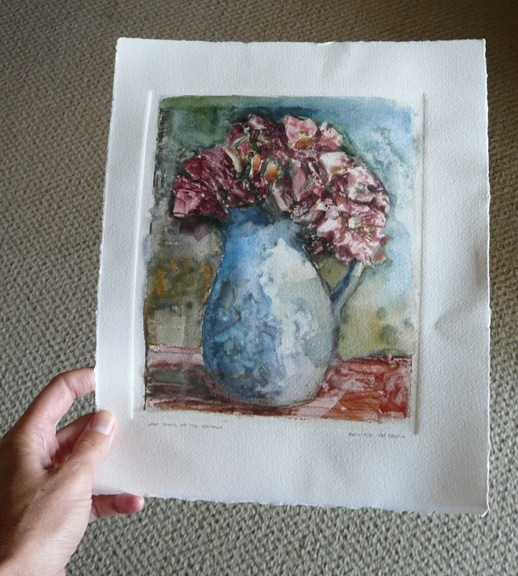 a hand holding a sheet of printmaking paper in the light with a monotype of a vase of roses in a loose, painterly style