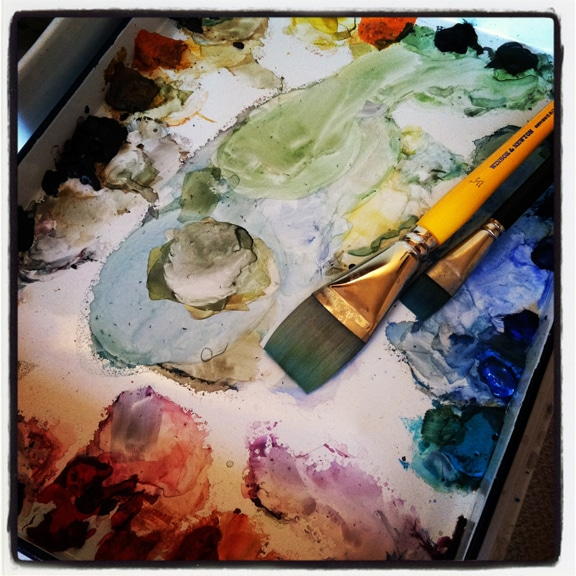 a watercolor palette with a flat brush sitting on it