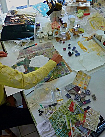 portrait collage underway with stamps, ink, paper and friends around a table