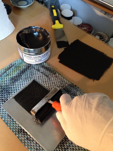 rolling out oil based printmaking ink on a zinc plate to create a dark field monotype