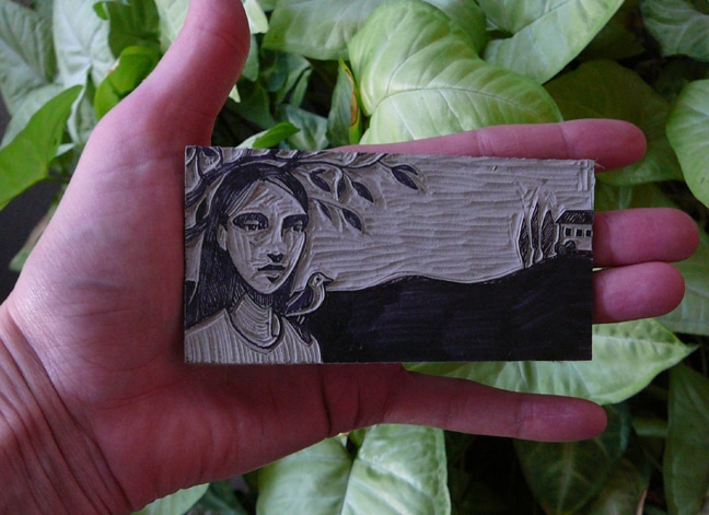 a tiny scrap of linoleum carved into a portrait of a girl with a bird on her shoulder and a house in the distance, by Belinda Del Pesco