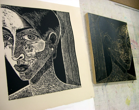 woodcut print next to the block it was printed from, featuring a woman's face on three quarters view
