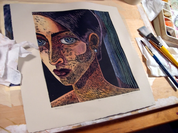 Adding watercolor to woodblock prints on an artist's table