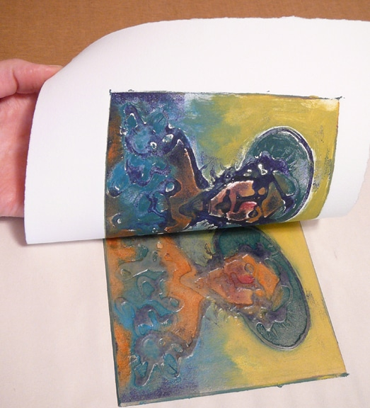 pulling a glue collagraph plate after a trip through the press