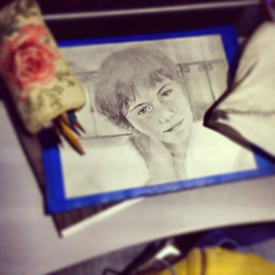 a sketch of a little girl's face in process on an airplane seat tray with a little bag of pencils