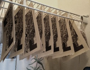 linocut prints drying on a closet maid rack with clothes pins