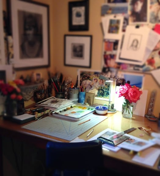 an art studio table nestled into a corner of a room with art supplies everywhere
