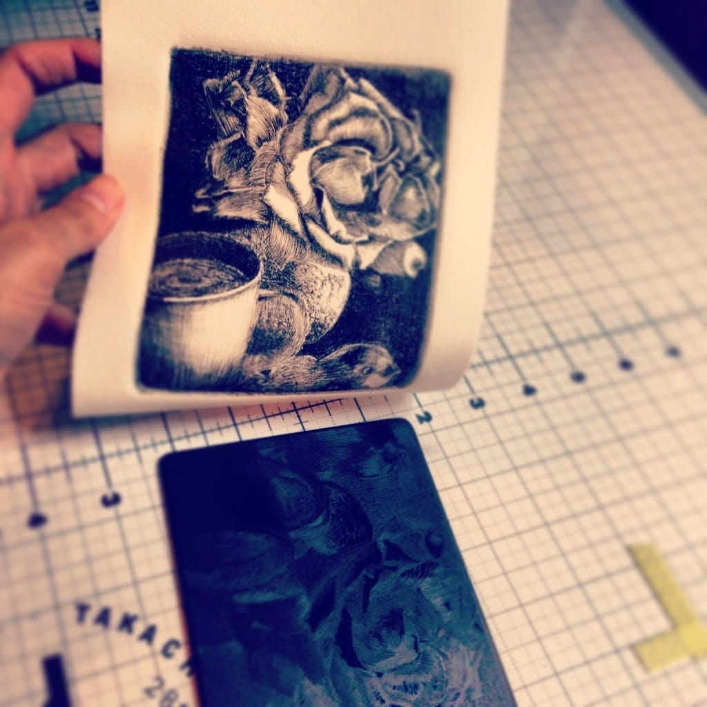 pulling a drypoint print from a sheet of black plexiglass after a trip through a printing press, where the line work on the plate has transferred to the paper revealing a still life of a rose, a cup and a bird figurine