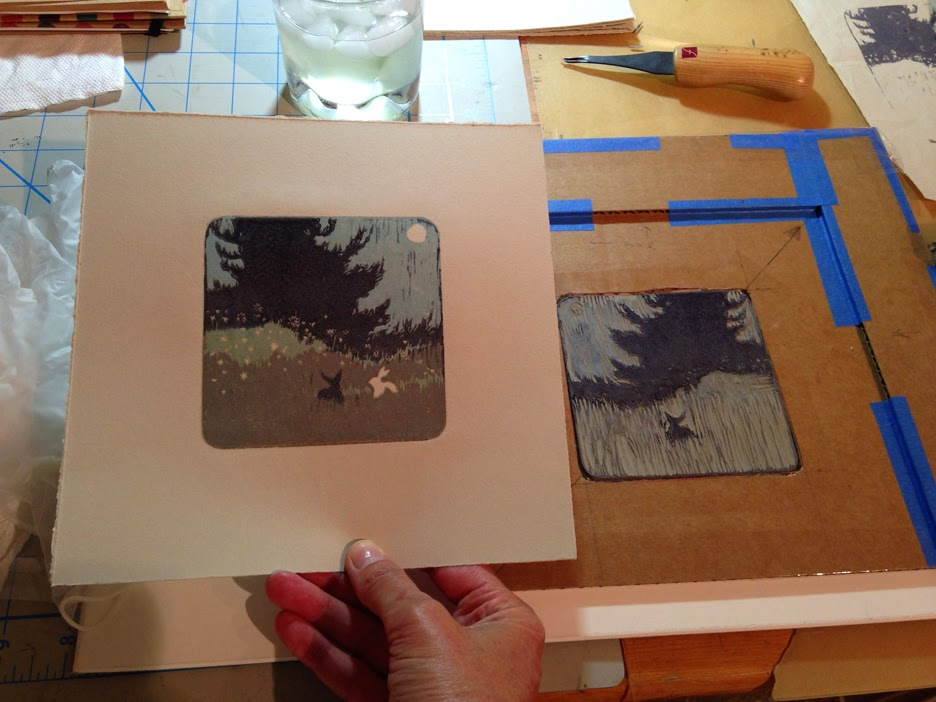 printing the last and darkest color on a reduction linocut of two rabbits in a meadow