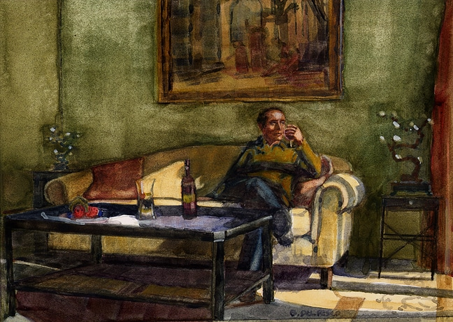 A man sipping wine in late afternoon sunlight on a couch in an olive green room with art and sculpture around him