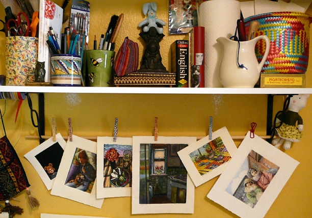 a shelf in an art studio with supplies tucked along it's length, and a line with clothe pins holding a variety of monotype prints