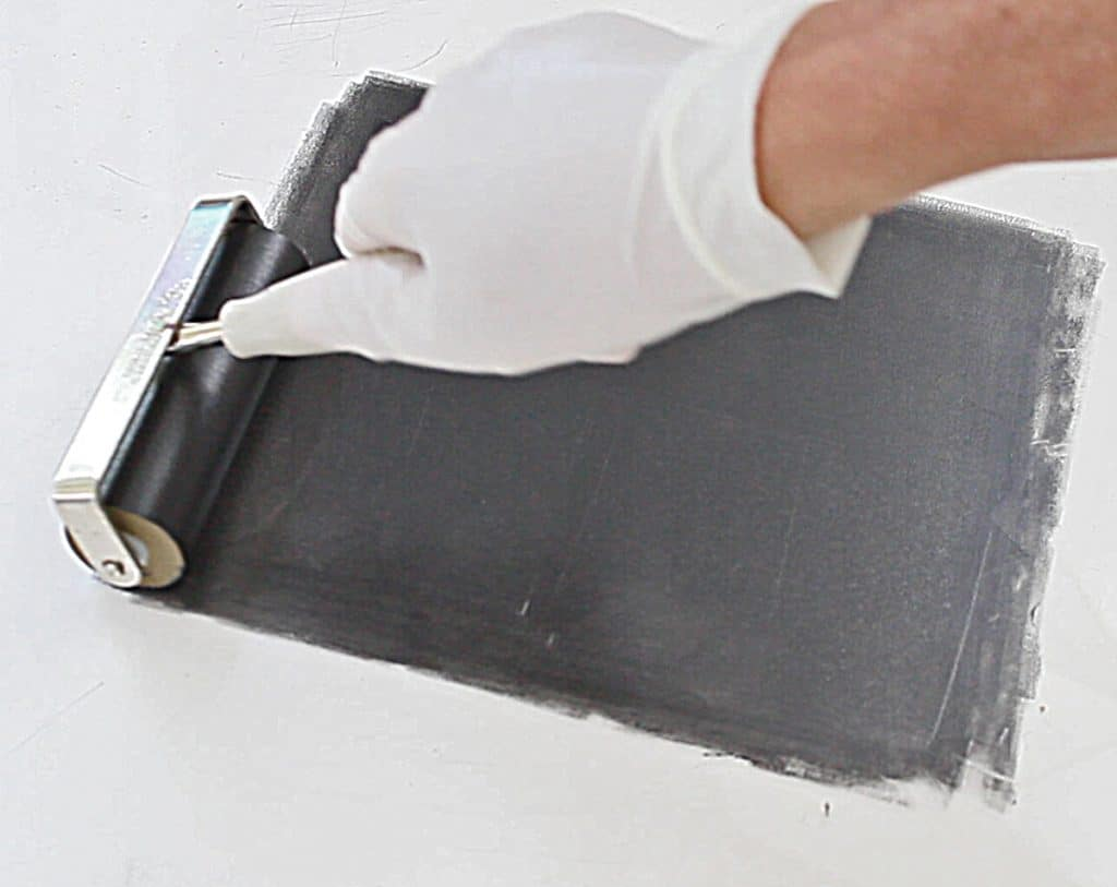 rolling out printmaking ink on a plexiglass surface to make a print