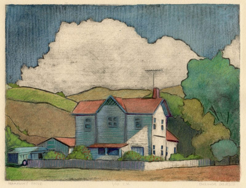 a collagraph print of a house surrounded by a picket fence in a meadow near a stand of trees with puffy clouds in the background