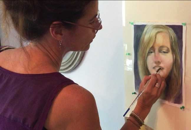 belinda del pesco painting a portrait in watercolor standing upright while the work in process is tacked to a wall