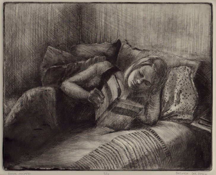 A drypoint etching of a young woman lounging against a pile of pillows in a bed reading a book