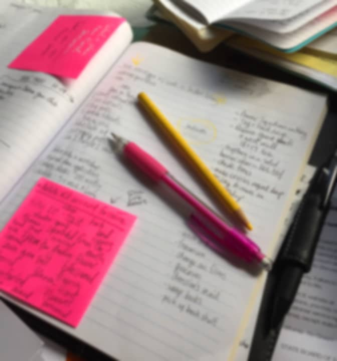a note pad with lists and post it notes