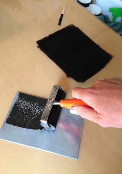 a zinc plate, with a loaded brayer rolling black ink over the surface