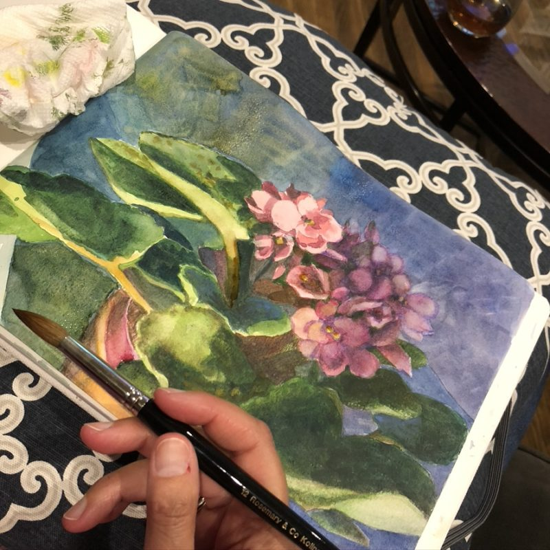a watercolor sketchbook open with a watercolor painting in process of african violets