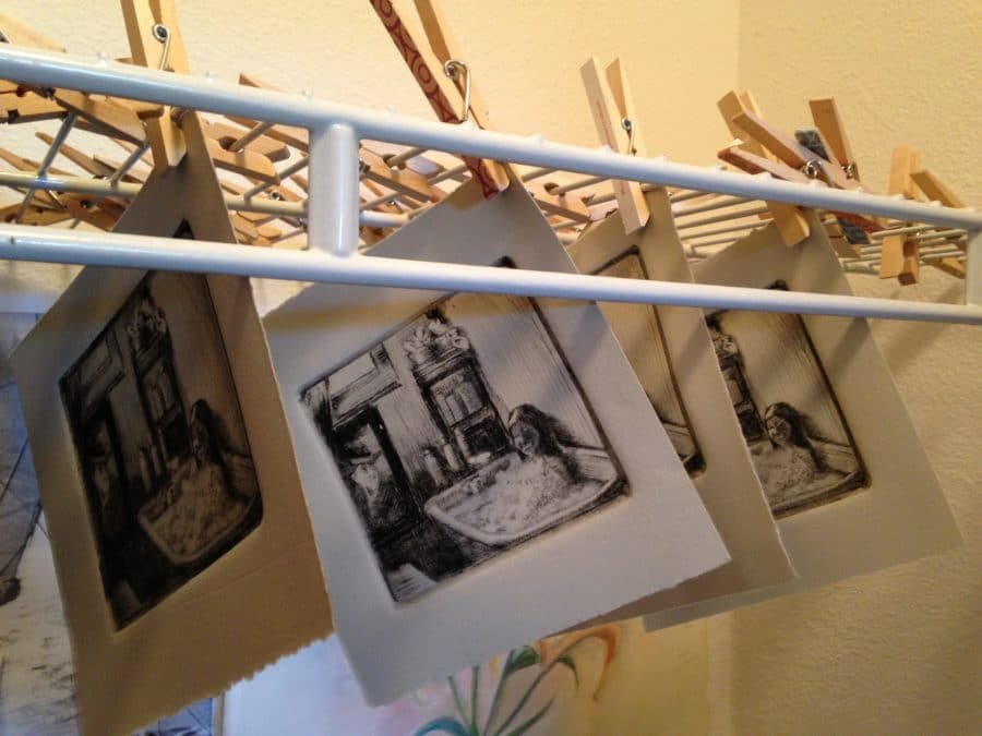 Drypoint etchings of a girl in a tub drying in an art studio
