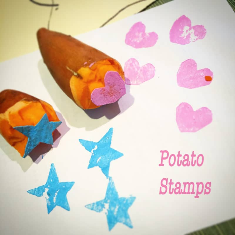two sweet potato halves carved into stamps. One with a star and the other with a heart, dipped in blue and pink paint, and stamped in multiple impressions on a sheet of paper