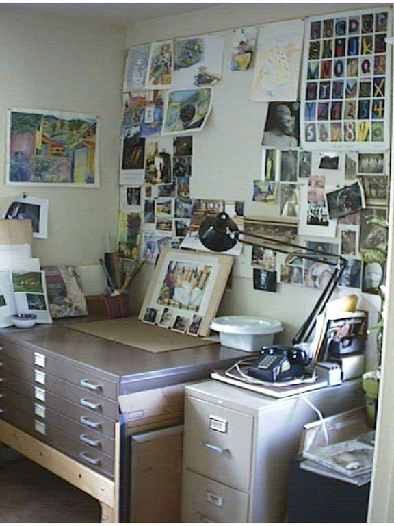 a messy artists studio with an old telephone and lots of art pinned to a wall above a set of HON flat files