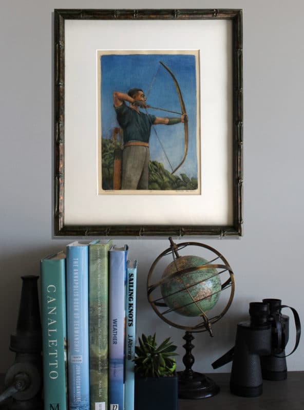 an archer, pulling his bow, loaded with an arrow, in a frame, on a wall near books and a globe