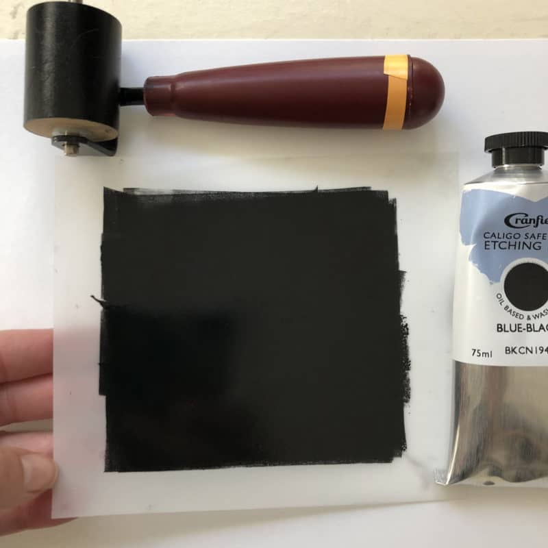 Rolling Caligo Safe Wash etching ink onto a small piece of drafting film