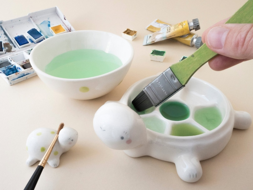 an artist gift of a ceramic paint palette and brush holder in the shape of a turtle