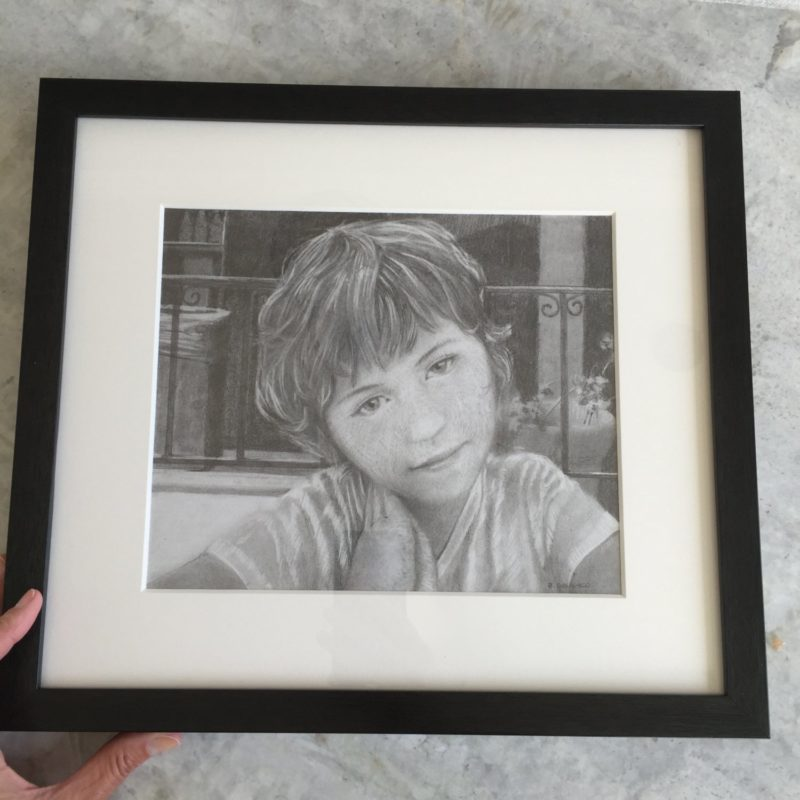 a framed pencil drawing of a little girl's face with her hands pressed together under her chin