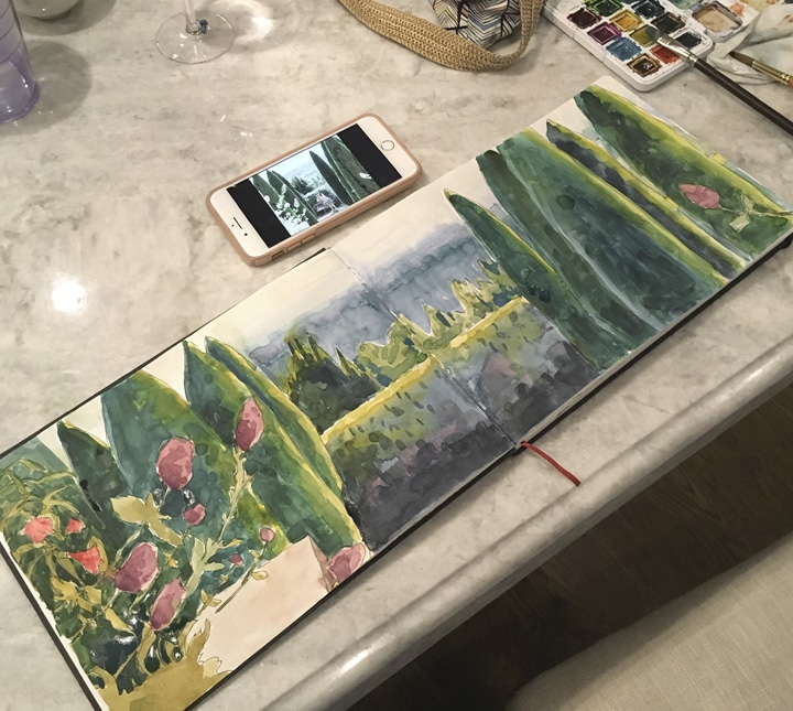 a sketchbook opened to a double-wide watercolor study on a kitchen counter, with a cell phone reference photo and the foot of a wine glass visible