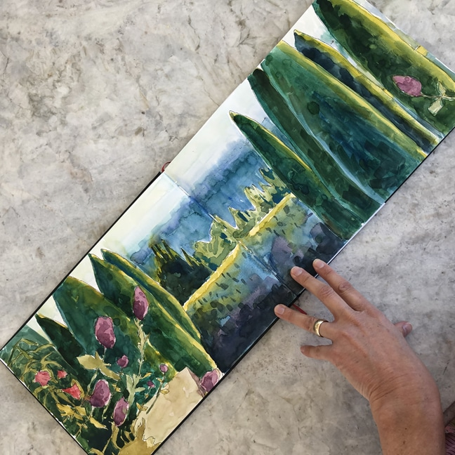 A hand holding a sketchbook open in a broad horizontal format showing a watercolor landscape study