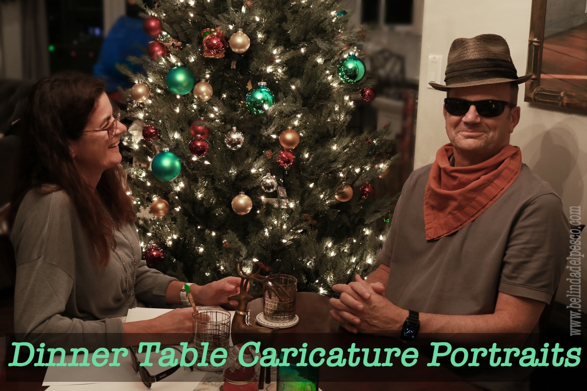 dinner table caricatures are an excellent art activity for hanging out and digesting before dessert. A woman seated near a Christmas tree is drawing with paper and pencil and laughing at her subject - a man in hat and sunglasses wearing a kerchief and snickering.