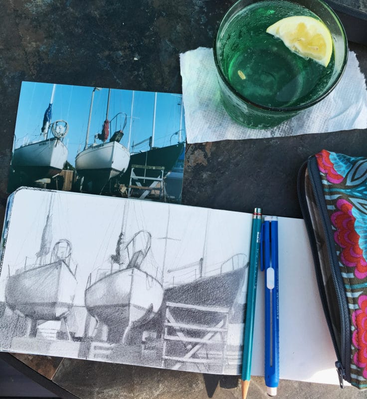 Sketching boats in a boat yard in pencil in a small moleskine sketchbook