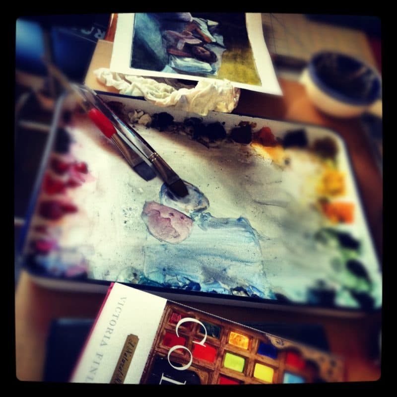 a watercolor palette made from a butcher's tray, with a brush resting in it, and a watercolor painting underway on a table nearby