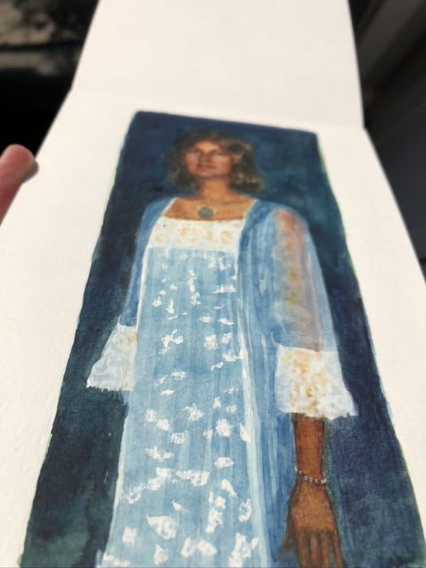 a figurative watercolor of a girl on a blue dress, painted in a moleskine watercolor pad