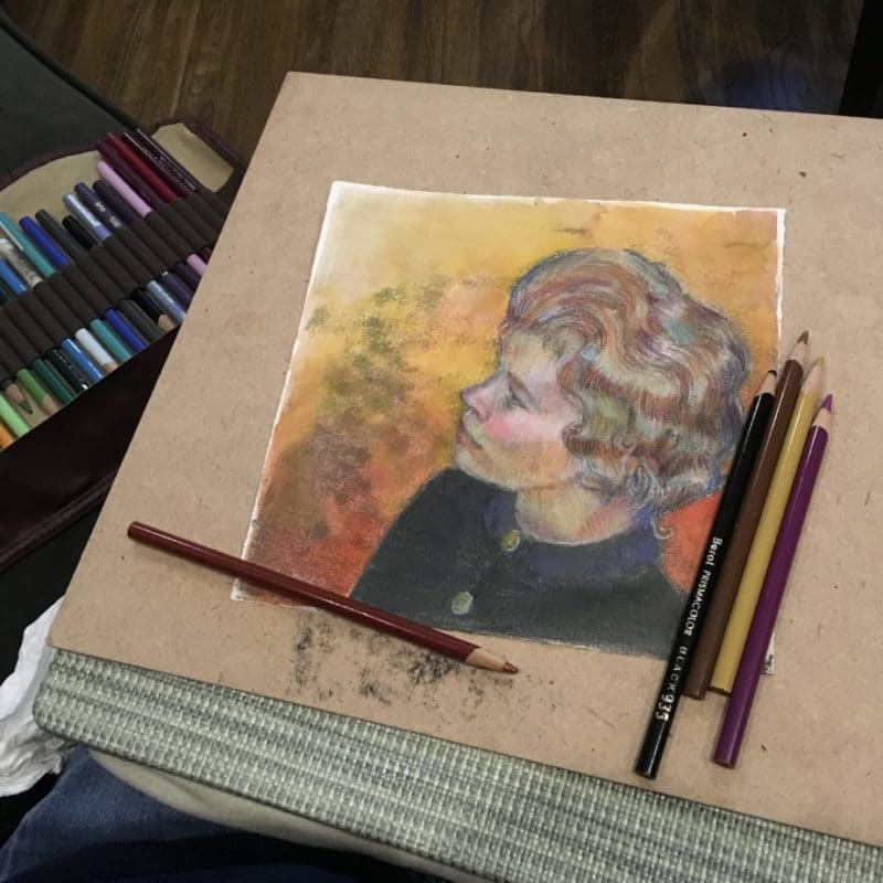 the same transfer drawing monotype as above, on a board, on a lap desk, on the couch with colored pencils nearby and a glass of wine off camera.