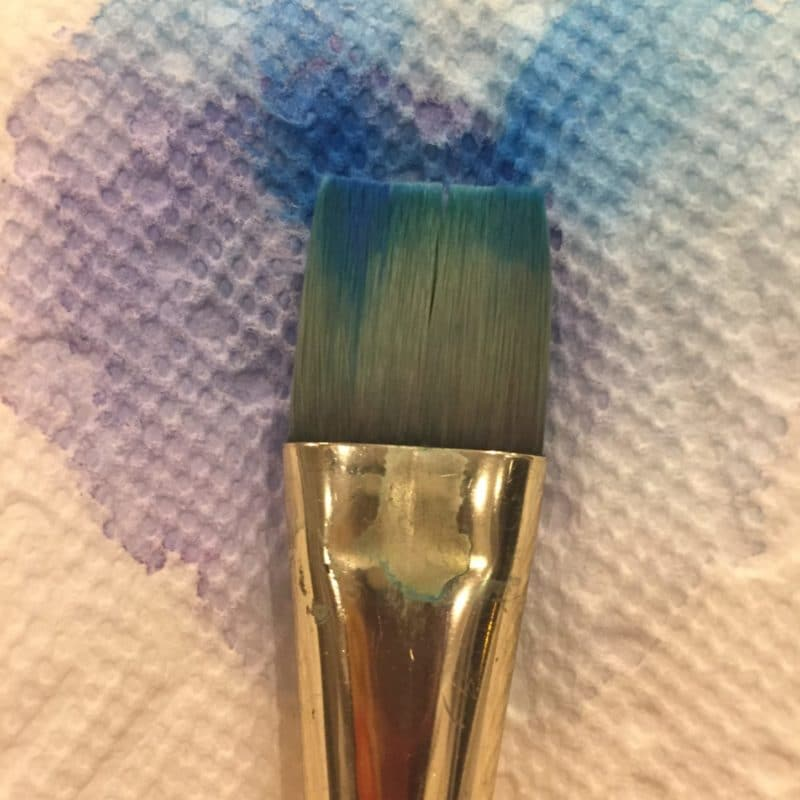a paint brush laying against a apper towel with watercolor that has seeped from the brush and bloomed all over the paper towel in purple and blue